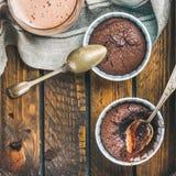 Chokladsouffle i bakningkoppar och mockakaffe, fyrkantig skörd Arkivfoto