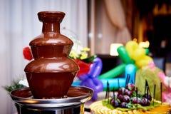 Chokladspringbrunn på en suddig bakgrund med nya frukter royaltyfria bilder