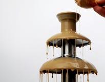 Chokladspringbrunnen av kondenserat mjölkar, isolerat på vit bakgrund Läcker fondueefterrätt royaltyfri bild