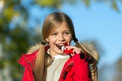 Chokladstång hennes trofé på den halloween dagen Trick eller söt choklad för fest Lag för ungeflickakläder för nedgångsäsong barn arkivfoto