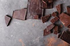 Chokladstora bitar och kakaopulver Stycken för chokladstång En stor stång av choklad på grå färger gör sammandrag bakgrund royaltyfria foton