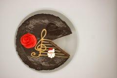 Chokladt?rta p? en vitbakgrund Bild fr?n ?ver Kakan dekoreras med en r?d blomma av kr?m och en stiliserad musikalisk st royaltyfri foto