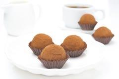 Chokladtryfflar på en platta och en kopp kaffe Royaltyfri Bild