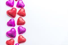 Chokladvalentinhjärtor som slås in i rött och rosa färger, omkullkastar på vänster sida av vit bakgrund arkivbild