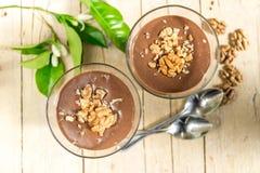 Chokladvaniljpudding med valnötter i ett exponeringsglas Arkivfoto