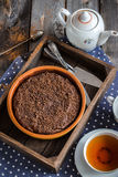 Chokolate cake in wooden box and cup of tea. Selective focus. Wooden background Royalty Free Stock Images
