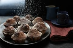 Cholate Mufins with a cloud of flour on black backgroundGROUND royalty free stock image
