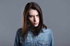 Choleric young woman. Anger. Furious young woman standing against grey background and looking at you Royalty Free Stock Photos