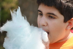 Chomp!. Teenager takes a mouthful of blue cotton candy at a fair stock images