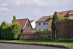 Chomutov, República Checa - 23 de abril de 2018: poca casa de madera marrón en jardín delante de casas de la familia en el stree  fotos de archivo