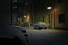 Chomutov, república checa - 22 de janeiro de 2018: carros entre casas na rua de Lidicka sob a neve na noite do inverno no styliza Fotografia de Stock Royalty Free
