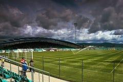Chomutov, República Checa - 1 de julio de 2017: riego de un campo de fútbol cuando los jugadores llegan en echada y spectat Fotos de archivo libres de regalías