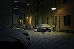 Chomutov, Tsjechische republiek - 22 Januari, 2018: auto's tussen huizen in Lidicka-straat onder sneeuw in de winteravond in HDR- Royalty-vrije Stock Fotografie
