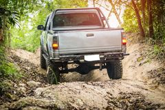 4 wheel drive in the forest. Chon Buri, Thailand-Dec 5, 2017: A 4 wheel drive is climbing on a difficult off-road in mountain forests in Thailand Royalty Free Stock Photos