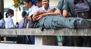 CHONBURI, TAILANDIA 3 AGOSTO 2017: Menzogne uniforme degli studenti militari di usura degli scolari su un banco fatto di cemento  Fotografia Stock Libera da Diritti