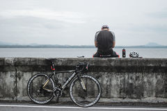 CHONBURI, THAILAND - AUGUST 5, 2015: Man resting on the edge dam with his bicycle Royalty Free Stock Photography