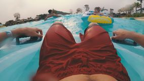 Pov view of Man floating on inflatable circle in the pool with artificial waves. CHONBURI, THAILAND, JANUARY 22, 2018: Pov view of Man floating on inflatable stock video