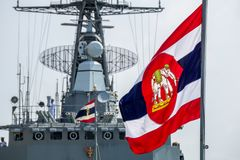 Royal Thai Navy ensign blow on flag pole with Royal Thai Navy Frigate in the background. CHONBURI, THAILAND - MARCH 15, 2018 : Royal Thai Navy ensign blow on Stock Photos