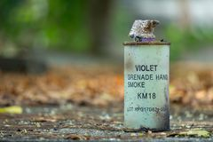 Used violet colour KM-18 smoke hand grenade put on the concrete stock photography