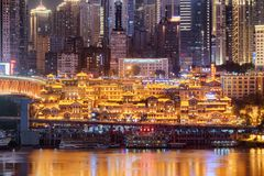Amazing night view of the Hongya Cave on skyscrapers background. Chongqing, China - September 29, 2017: Amazing night view of the Hongya Cave on skyscrapers royalty free stock photos