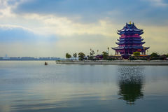 CHONGYUANG TEMPLE, CHINA: Temple tower in blue and pink color, sitting on land next to nice lake, peaceful morning mood Stock Photos