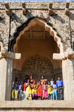 Chool class with teacher posing under the arch of Elephant Stables at Hampi Royalty Free Stock Photos