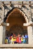 Chool-Klasse mit dem Lehrer, der unter dem Bogen von Elefant-Ställen bei Hampi aufwirft Lizenzfreie Stockfotos