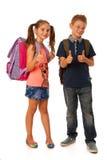 Choolboy и школьница при schoolbags изолированные над задней частью белизны Стоковая Фотография RF