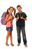 Choolboy и школьница с schoolbags над задней частью белизны Стоковые Фотографии RF