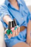Choose any!. Close-up of a female hand giving nailpolish Royalty Free Stock Image