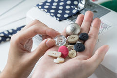 Choose buttons in woman hands , close up Stock Photos
