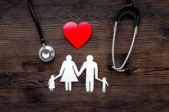 Choose family health insurance. Stethoscope, paper heart and silhouette of family on dark wooden background top view