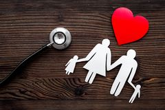 Choose family health insurance. Stethoscope, paper heart and silhouette of family on dark wooden background top view Stock Image