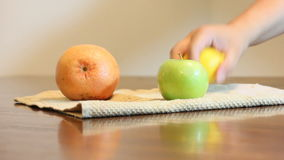 Choose fruit. Young hands reach into a pile of fruit and take them one by one stock video