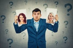 Choose girlfriend. Undecided young men holding two photos has to choose between two woman, question marks around head. Girlfriend partner first date choice love stock images