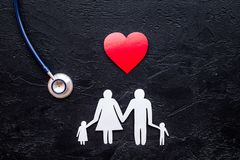 Choose health insurance. Stethoscope, paper heart and silhouette of family on black stone background top view copyspace Royalty Free Stock Photography