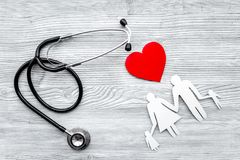 Choose health insurance. Stethoscope, paper heart and silhouette of family on grey wooden background top view Stock Image