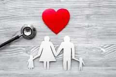 Choose health insurance. Stethoscope, paper heart and silhouette of family on grey wooden background top view copyspace Stock Image