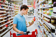 Choose healthy food. Young handsome man reading label on olives in supermarket Royalty Free Stock Photography