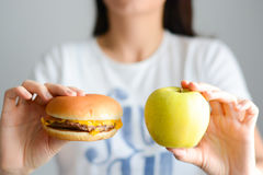 Choose between junk food versus healthy diet. Choose between junk food and a healthy lifestyle Royalty Free Stock Image