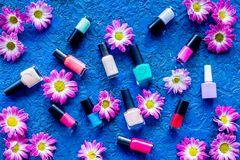 Choose nail polish for manicure. Bottles of colored polish on blue background top view Stock Photo