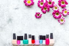 Choose nail polish for manicure. Bottles of colored polish on grey background top view copyspace Stock Photo