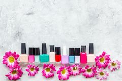 Choose nail polish for manicure. Bottles of colored polish on grey background top view copyspace Royalty Free Stock Photos