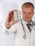 Choose one pill. A young cardiologist show drugs and wink Stock Photo