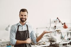 Choose it. Portrait of cheerful male jeweler wearing apron gesturing while standing in his jewelry making studio. Business. Jewelry workshop stock images