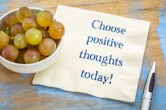 Choose positive thoughts today!. Inspirational handwriting on napkin with fresh grapes stock photography