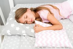 Choose proper pillow to relax well. Healthy sleep tips. Girl sleeps on little pillow bedclothes background. Girl child. Long hair fall asleep pillow close up stock photography