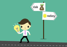 Choose risk for hight return. Businessman carry lightbulb by right hand and walking on road and signs with word risk and safety Royalty Free Stock Image