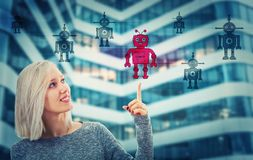 Choose robot. Beautiful blonde woman pointing her finger up choosing a different robot. Employee choice, group of artificial intellect replace human, leadership stock photo