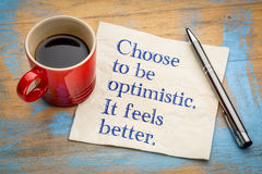 Choose to be optimistic. It feels better. Choose to be optimistic.. It feels better. Handwriting on a napkin with a cup of espresso coffee Royalty Free Stock Photography